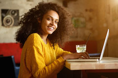 Smiling young african woman sitting in a cafe with laptop Royalty Free Stock Photo