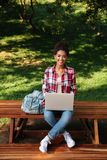 Smiling young african woman sitting outdoors in park. Image of smiling young african woman sitting outdoors in park. Looking camera using laptop computer Royalty Free Stock Photo