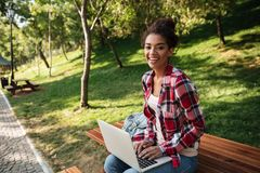 Smiling young african woman sitting outdoors in park. Image of smiling young african woman sitting outdoors in park. Looking camera using laptop computer Royalty Free Stock Image