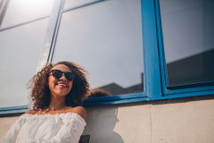 Smiling young african woman sitting outdoors. Shot of happy young african woman sitting outdoors looking away and smiling. Female wearing sunglasses sitting Stock Images