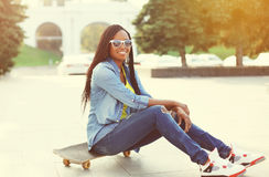smiling young african woman with skateboard in city Stock Photography