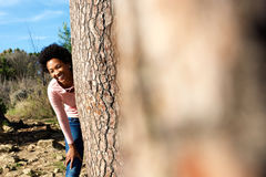 Smiling young african woman standing behind a tree Stock Image