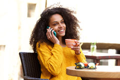 Smiling young african woman talking on cellphone at cafe Stock Photo