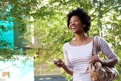 Smiling young african woman walking with mobile phone and purse Royalty Free Stock Image