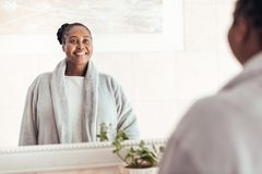 Smiling young African woman standing at her bathroom mirror. Smiling young African woman wearing a robe looking at her reflection in a mirror while standing in royalty free stock images