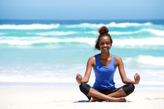Smiling young african woman in yoga pose Royalty Free Stock Image