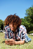 Smiling young afro man lying down on grass in park holding phone Stock Photos