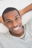 Smiling young Afro man resting in bed Stock Photography