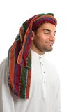 Smiling young arab man. Smiling adult arab middle eastern mixed race man in traditional clothing.  He is looking down.  Suitable for a message.  White background Royalty Free Stock Images