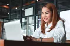 Smiling young Asian business woman with laptop working in modern office royalty free stock images