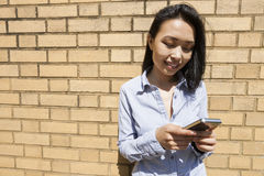 Smiling young asian businesswoman text messaging on cell phone against brick wall Stock Photos