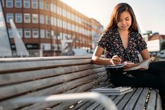 Smiling Asian college student sitting on campus studying between classes. Smiling young Asian college student sitting outside on a bench on campus between royalty free stock photo