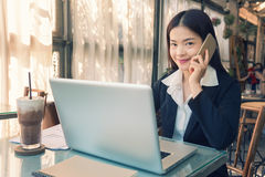 Smiling young asian executive business woman using her cell phon Royalty Free Stock Images