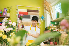 Smiling young asian florist man making bunch at flower shop stock image