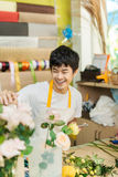 Smiling young asian florist man making bunch at flower shop Royalty Free Stock Images