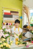 Smiling young asian florist man making bunch at flower shop Stock Photography