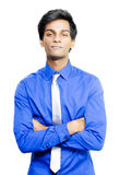 Smiling young Asian male business person. Happy young Asian male business person standing smiling with his arms folded over his chest isolated on a white Royalty Free Stock Photos