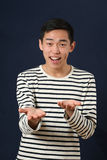 Smiling young Asian man gesturing with two hands Royalty Free Stock Images