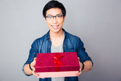Smiling young asian man with gift box Royalty Free Stock Image