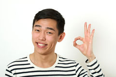 Smiling young Asian man giving the okay sign and looking at came Royalty Free Stock Photos