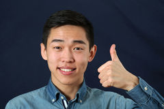 Smiling young Asian man giving the thumbs up sign Stock Photography