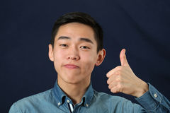 Smiling young Asian man giving the thumbs up sign Royalty Free Stock Image