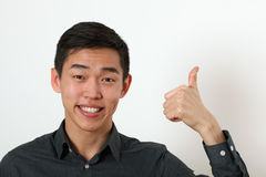 Smiling young Asian man giving the thumbs up signs and looking a Stock Photo