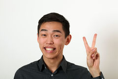 Smiling young Asian man giving the victory sign and looking at c Royalty Free Stock Photography