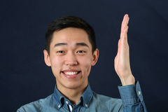 Smiling young Asian man holding his hand upright Stock Images