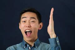 Smiling young Asian man holding his hand upright Stock Photography