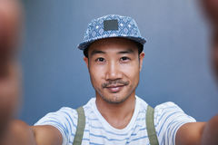 Smiling young Asian man taking a selfie outside Royalty Free Stock Images