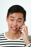 Smiling young Asian man using a smartphone Royalty Free Stock Photos