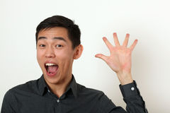 Smiling young Asian man waving his palm and looking at camera Royalty Free Stock Image