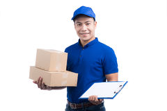 Smiling young asian salesman with parcel and clipboard against a stock photos