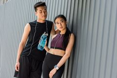smiling young asian sportsman with earphones over neck standing near sportswoman with sport bottle of water royalty free stock photo