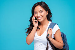 Smiling young asian woman with backpack talking on cellphone stock image