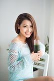 Smiling young asian woman drinking green fresh vegetable juice o stock image