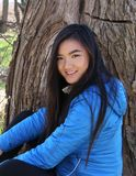 Smiling Young Asian Woman in Forest. A young Asian woman smiles for the camera in a forest setting Stock Photo