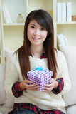 Smiling young asian woman with a gift box Stock Photos