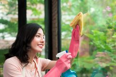 Smiling young asian woman housewife washes a window Royalty Free Stock Photo