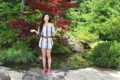 Smiling Young Asian Woman Model Stands in a Park with Arms Raised Royalty Free Stock Photography