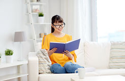 Smiling young asian woman reading book at home Stock Images
