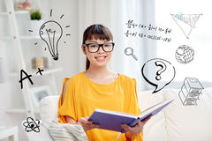 Smiling young asian woman reading book at home. Education, knowledge, vision, literature and people concept - smiling young asian woman or student girl in Stock Photo