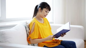 Smiling young asian woman reading book at home stock footage