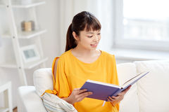 Smiling young asian woman reading book at home Royalty Free Stock Photography