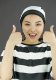 Smiling young Asian woman showing thumb up sign with both hands in prisoners uniform Royalty Free Stock Image