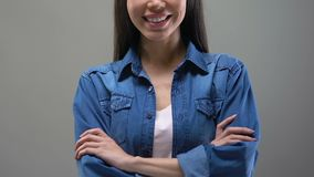 Smiling young Asian woman standing with hands crossed and looking to camera stock video