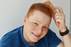 A smiling young attractive freckled man with trendy hairdo combing his red hair with a comb wearing blue shirt and watch isolated Stock Images