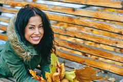 Smiling young attractive woman with autumn maple leaves in park at fall outdoors Stock Photos