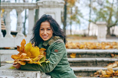 Smiling young attractive woman with autumn maple leaves in park at fall outdoors. Young attractive woman with autumn maple leaves in park at fall outdoors royalty free stock photos